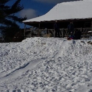 Sledding in front of the Double Cottage at Noble View Outdoor Center